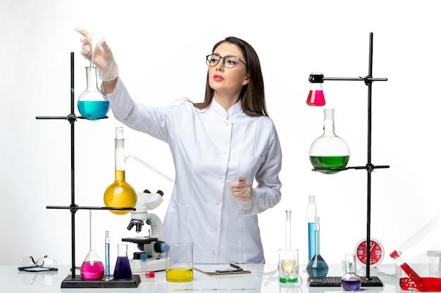 Química feminina em traje médico esterilizado, de frente, trabalhando com soluções em ciência da covidemia de vírus de laboratório de fundo branco