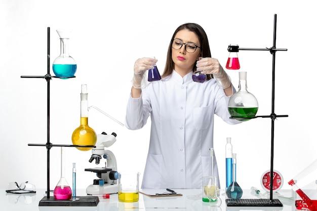 Química feminina em traje médico esterilizado segurando frascos com soluções roxas em fundo branco.