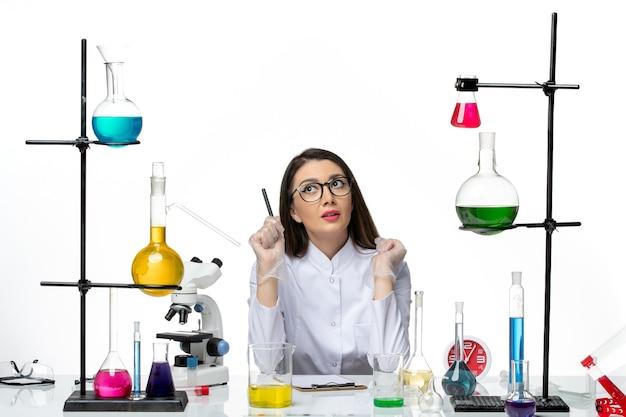 Química feminina em um terno médico branco sentada de frente com soluções em um piso branco. covid- science pandemic lab virus