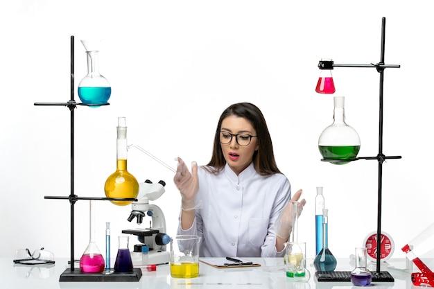 Química feminina em um terno médico branco sentada de frente no fundo branco.