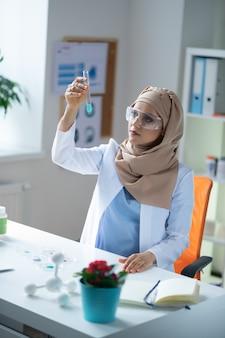 Química feminina. química feminina usando hijab e uniforme sentada e olhando para o tubo de ensaio