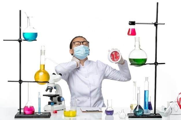 Química feminina vista frontal em traje médico com máscara segurando relógios e sofrendo de dor no fundo branco vírus laboratório química covid- splash