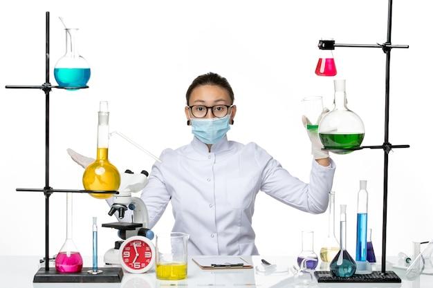 Química feminina vista frontal em traje médico com máscara segurando solução verde no piso branco respingo laboratório vírus química covid-