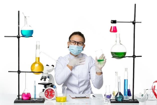 Química feminina vista frontal em traje médico com máscara segurando solução verde sobre fundo branco respingo laboratório vírus química covid-