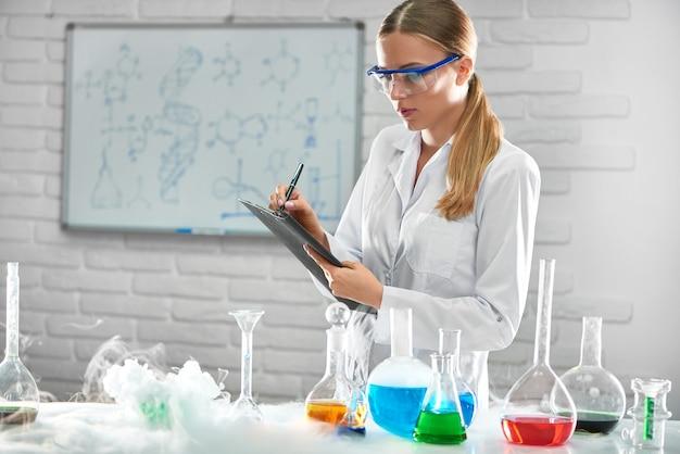 Química linda trabalhando no laboratório, testando amostras