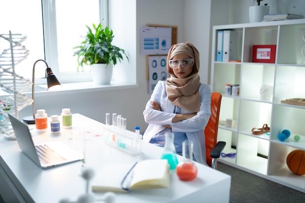 Químico cansado. química feminina vestindo hijab e uniforme branco, sentindo-se cansada após a análise das amostras