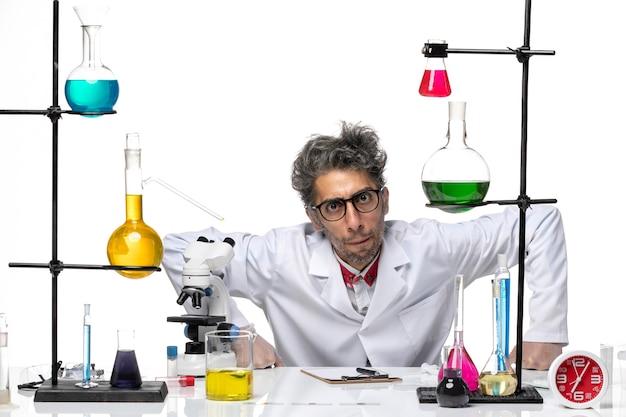 Químico de meia-idade de vista frontal em traje médico branco sentado com soluções