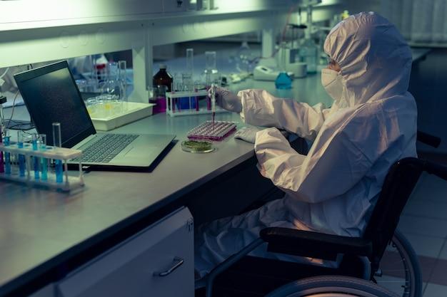 Químico deficiente em roupas de trabalho de proteção e máscara examinando líquido em tubos de ensaio na mesa do laboratório