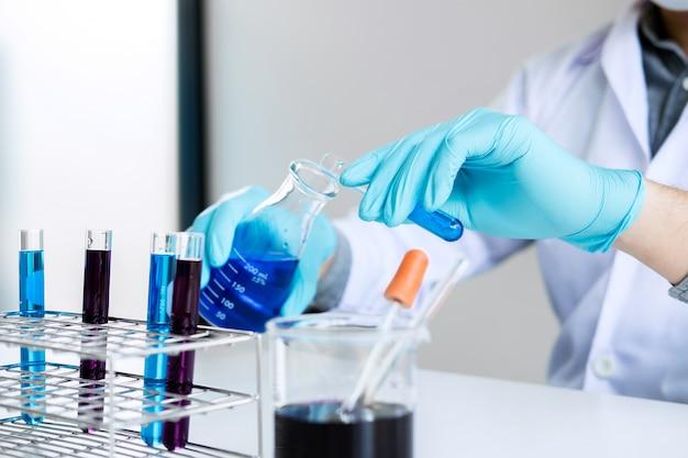 Químico está analisando amostra em laboratório com equipamentos e experimentos científicos vidro contendo
