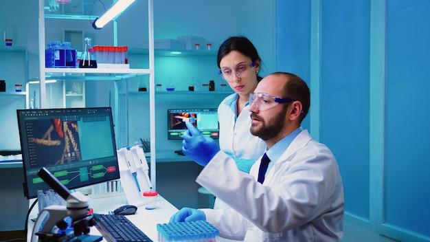 Químico explicando ao enfermeiro o desenvolvimento da vacina em um laboratório moderno e equipado, segurando um tubo de ensaio com amostra de sangue