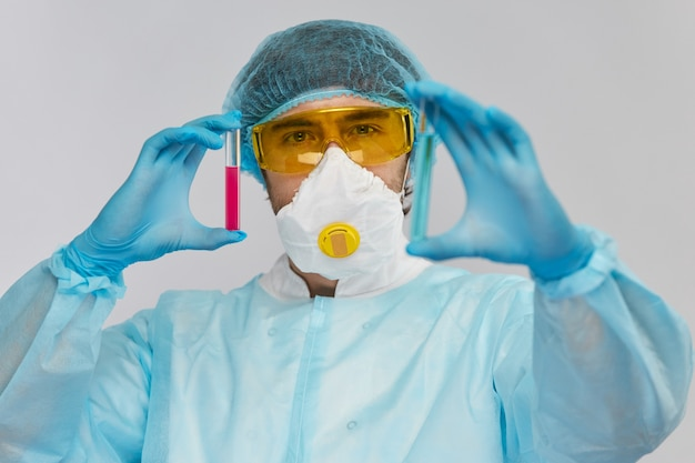 Químico masculino com tubos de ensaio de diferentes riscos biológicos coloridos