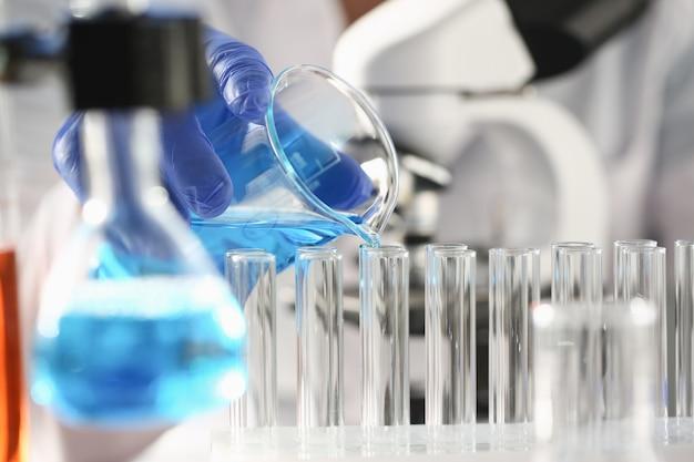 Químico masculino detém tubo de ensaio de vidro na mão transborda uma solução líquida de potássio