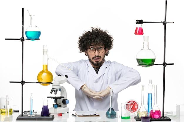 Químico masculino em terno médico, vista frontal, sentado em frente à mesa com soluções na mesa branca