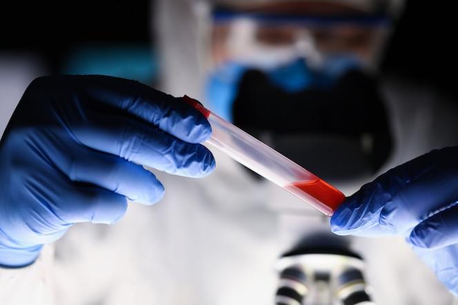 Químico masculino, examinando a amostra de sangue no laboratório escuro
