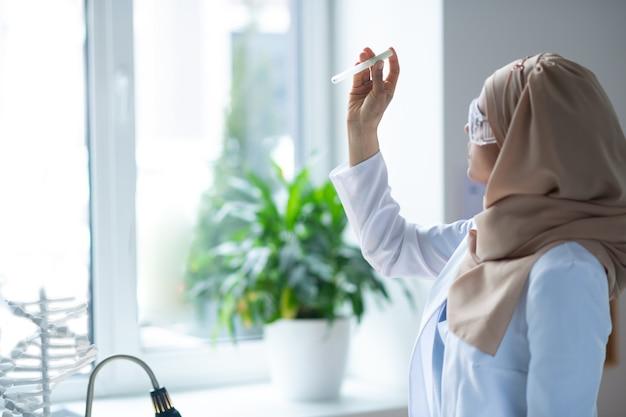 Químico perto da janela. químico usando hijab e óculos segurando um tubo de ensaio em pé perto da janela