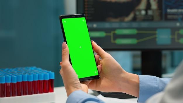 Químico profissional verificando os resultados do paciente no smartphone com tela verde, enquanto um colega de jaleco branco trazendo amostras de sangue. cientista em laboratório usando smartphone com display de chroma key de maquete