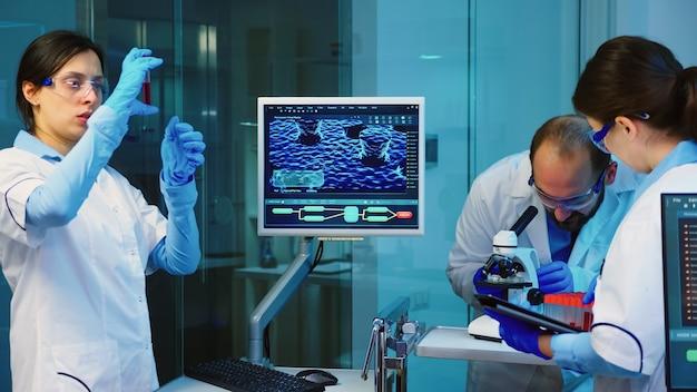 Químico sênior analisando amostra de sangue enquanto colegas de trabalho discutem