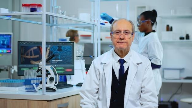 Químico sênior sentado em um moderno laboratório equipado, olhando satisfeito para a câmera. equipe multiétnica examinando a evolução do vírus usando ferramentas químicas e de alta tecnologia para pesquisa científica e desenvolvimento de vacinas