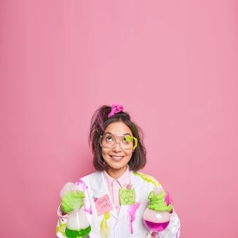Químico trabalha em laboratório de ciências conduz experimento químico segura frascos de vidro concentrados com expressão feliz acima isolados em rosa
