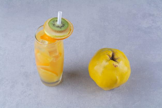 Quince um copo de suco de laranja na mesa de mármore.