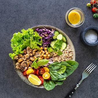 Quinoa, cogumelos, alface, repolho roxo, espinafre, pepino, tomate em uma tigela de buda