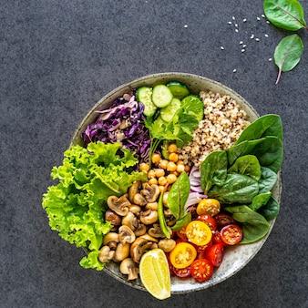 Quinoa, cogumelos, alface, repolho roxo, espinafre, pepino, tomate, uma tigela de buda em uma superfície escura, vista superior. delicioso conceito de nutrição balanceada