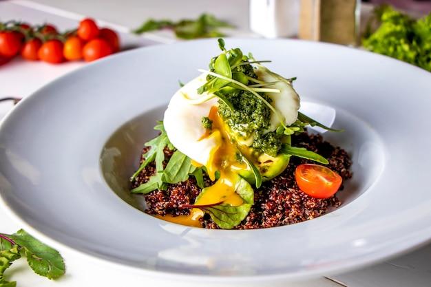 Quinoa com abacate, ovo escalfado e microgreen em um prato branco