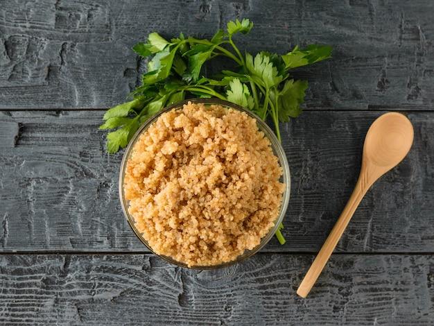 Quinoa fervida em uma tigela de vidro com uma colher em uma mesa de madeira preta
