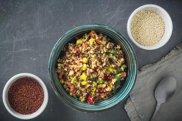 Quinoa saladeira com legumes: cenoura, milho, pimentão, ervilhas e duas tigelas com quinoa vermelho e branco