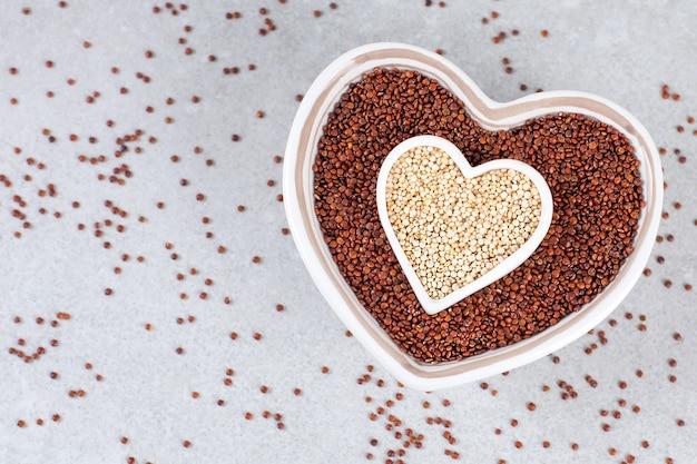 Quinoa vermelha e branca em uma tigela em forma de coração no fundo de pedra