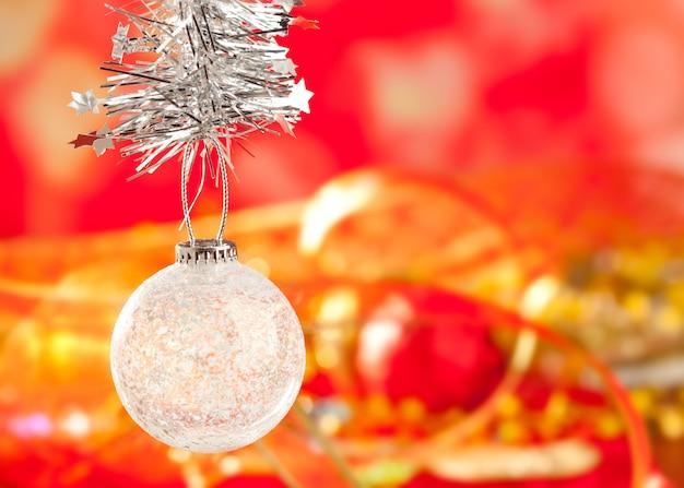 Quinquilharia de cristal da neve do ouropel do natal no vermelho