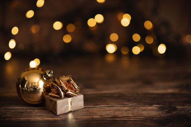 Quinquilharias de prata douradas bonitas do deco do natal com os presentes no fundo preto escuro. copyspace.