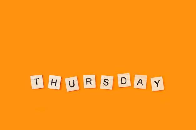 Quinta-feira, escreva com cubos de letras de madeira em um fundo de orage