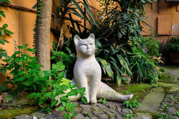 Quintal cheio de plantas com gato artificial