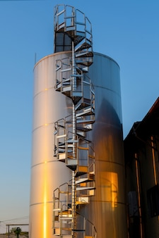 Quintal da vinícola ao pôr do sol com tanques de metal para armazenamento de vinho