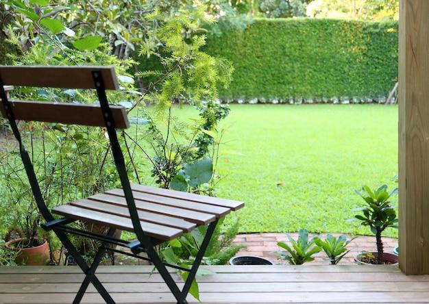 Quintal de gramado de grama verde brilhante com uma cadeira de madeira em primeiro plano