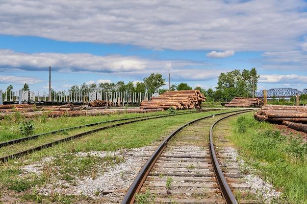 Quintal de uma fábrica de processamento de madeira com toras, montanhas de serragem e trilhos de trem