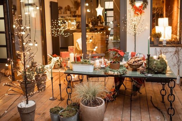 Quintal lindamente decorado de uma casa de campo com uma mesa de jantar festiva durante os feriados de ano novo