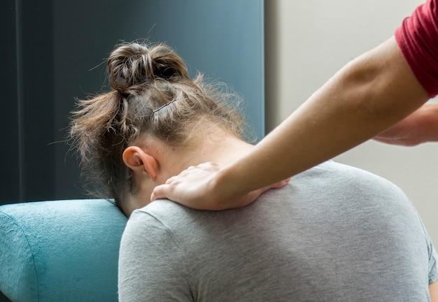 Quiroprático está fazendo uma massagem de escritório na cadeira