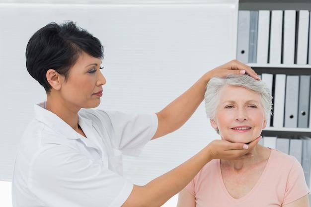 Quiroprático feminino fazendo ajuste de pescoço no consultório médico