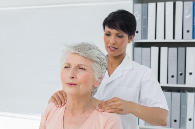 Quiroprático feminino massageando o ombro de uma mulher sênior no consultório médico