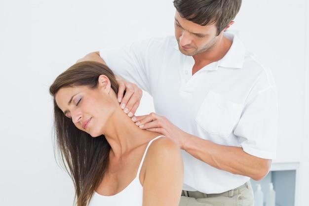 Quiroprático masculino massageando o pescoço de uma mulher jovem
