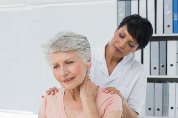 Quiroprático, olhar, mulher sênior, com, dor pescoço