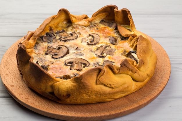 Quishe com cogumelos em uma placa de madeira