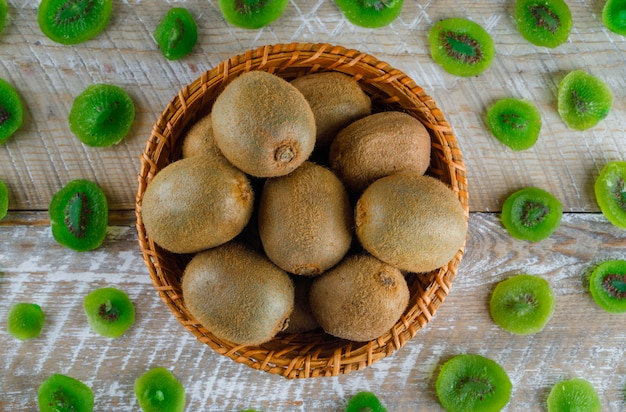Quivi com fatias de kiwi secas em uma cesta de vime na mesa de madeira, plana leigos.
