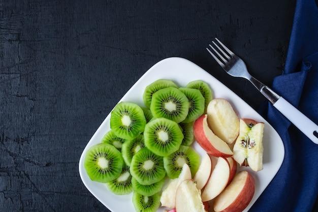 Quivi e maçãs frescos da fruta misturada com uvas em uma placa em uma tabela de madeira.