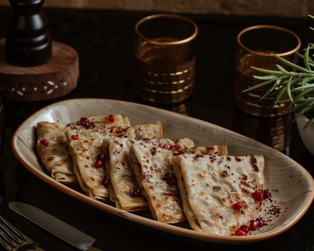 Qutab caucasiano, kutab, gozleme servido com sementes de romã em um prato de granito