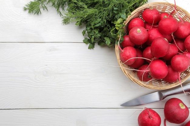 Rabanete fresco. rabanetes de legumes frescos de primavera e verduras frescas em uma mesa de madeira branca. ingredientes para cozinhar. fechar-se. vista do topo