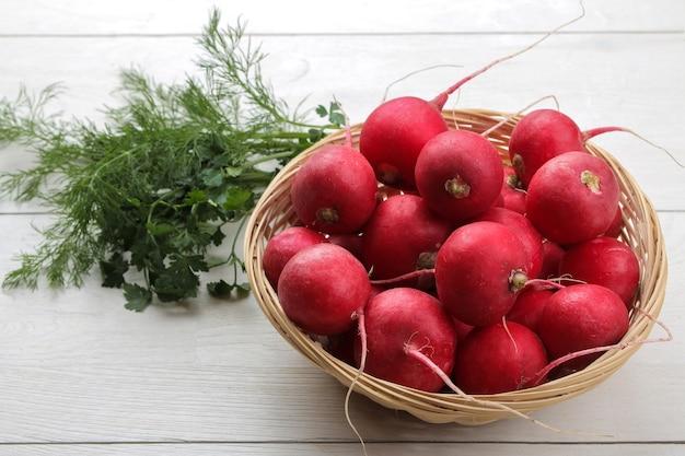 Rabanete fresco. rabanetes de legumes frescos de primavera e verduras frescas em uma mesa de madeira branca. ingredientes para cozinhar. fechar-se.