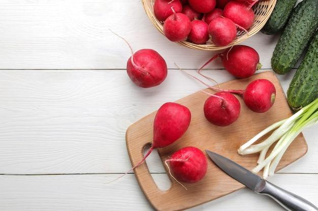 Rabanete fresco. rabanetes de legumes frescos de primavera, pepino, cebolinha e verdes em uma mesa de madeira branca. ingredientes para cozinhar. vista do topo